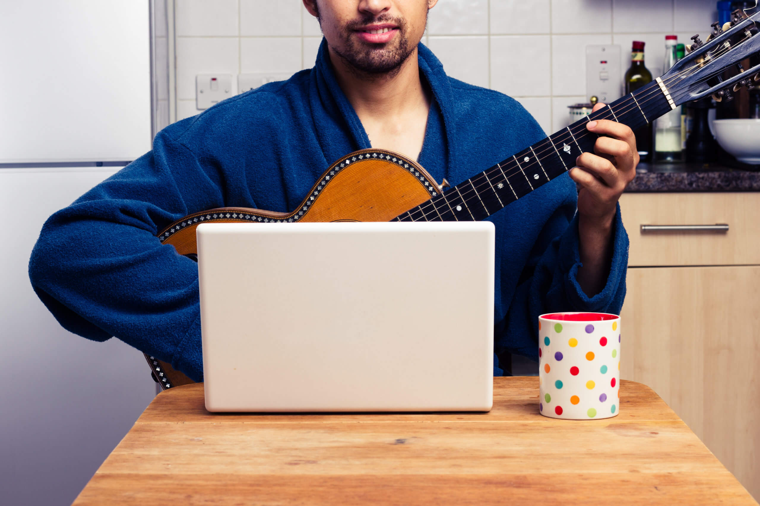man learning to play guitar in kitchen